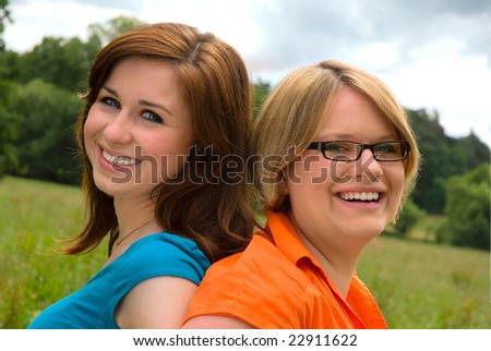 two smiling girls relaxing outdoor - stock photo