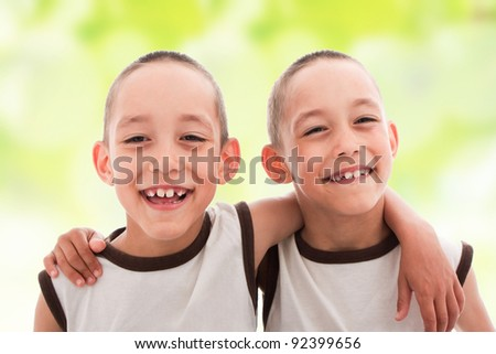 two smiling happy boys twins embrace one another on spring green background