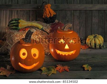 Two smiling jack-o-lanterns against a weathered fence - stock photo