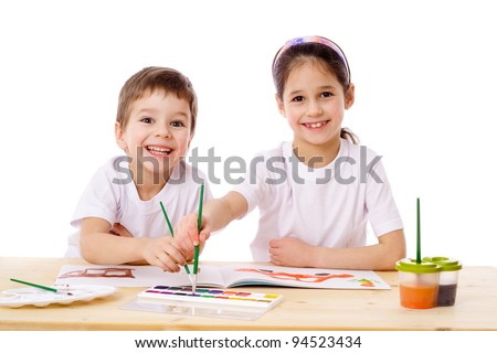 Two smiling kids at the table draw with watercolor, isolated on white