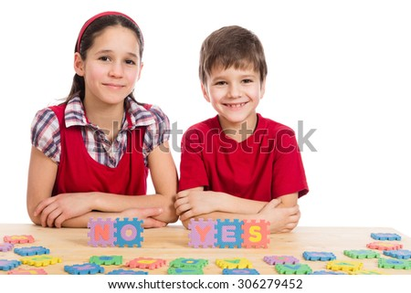 Two smiling kids at the table with puzzle letters, isolated on white - stock photo