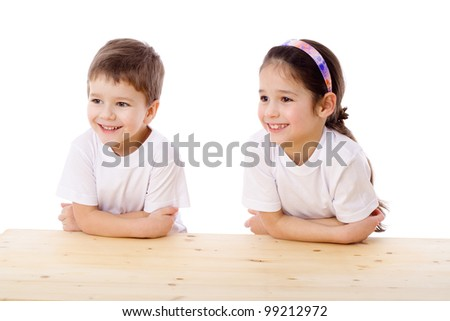 Two smiling kids sitting at the empty table and looking aside, isolated on white - stock photo