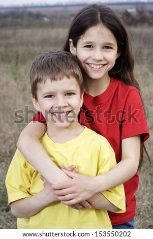Two smiling kids standing together on the autumn fields, outdoor - stock photo