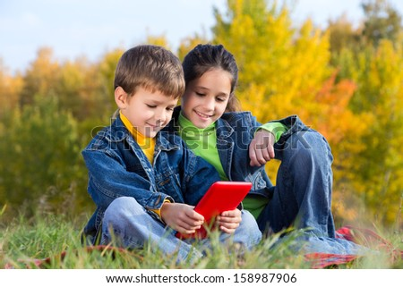 Two smiling kids with tablet pc sitting on the autumn lawn, outdoors - stock photo