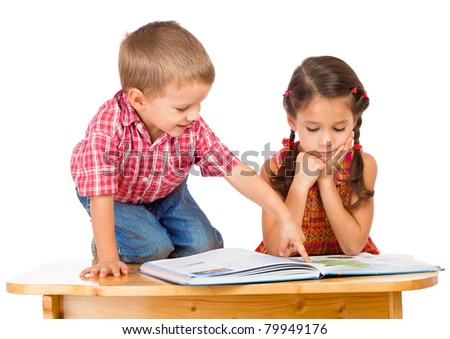 Two smiling little children reading book on the desk, isolated on white