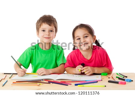Two smiling little kids at the table draw with crayons, isolated on white - stock photo