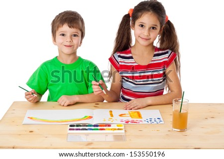 Two smiling little kids at the table drawing together, isolated on white - stock photo