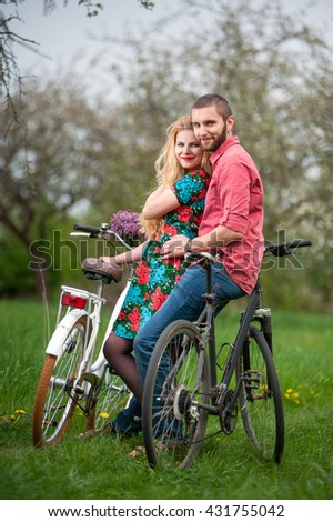 Two smiling lovers standing with bicycles and looking to the camera in the spring garden, against the background of trees and fresh greenery