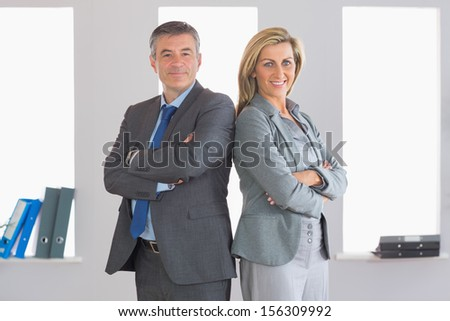Two smiling mature businesspeople looking at camera standing firmly back to back with crossed arms at office - stock photo