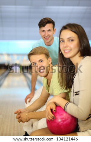 Two smiling men and woman with pink ball sit in bowling club; focus on center man; shallow depth of field - stock photo