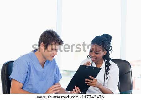 Two smiling nurses working on a professional clipboard in a well-lit room