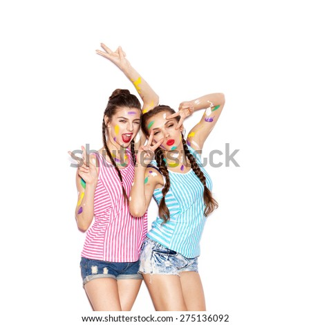 Two smiling painted girl friends fooled and having fun. White background not isolated - stock photo