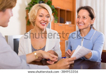 Two smiling positive female pensioners taking legal advice from public notary