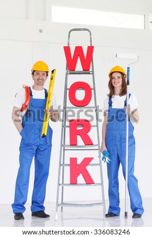 Two smiling professional workers with tools and WORK letters - stock photo