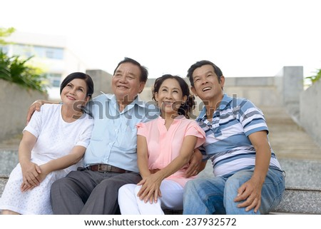 Two smiling senior couples sitting on the steps and looking up - stock photo