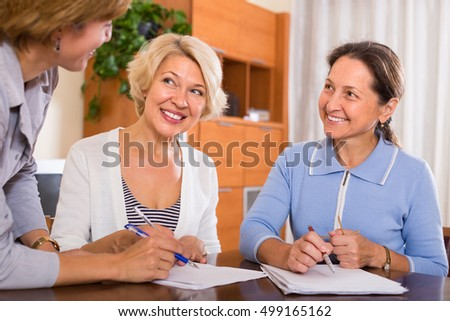 Two smiling senior ladies signing documents at bank
