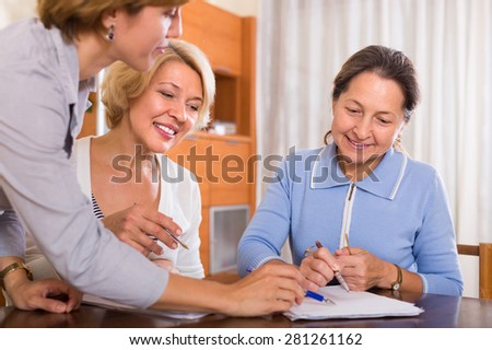 Two smiling senior ladies signing documents at bank with agent