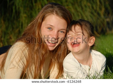 two smiling sisters: teenager and little girl