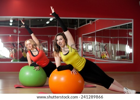 Two smiling sporty girls stretching, doing abdominal exercises on pilates fitballs - stock photo