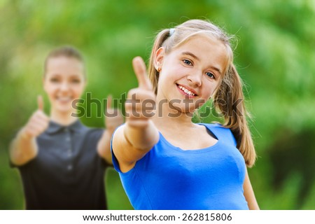 Two smiling teenage girs shows hand sign that it is doing fine, against background of green summer park. - stock photo