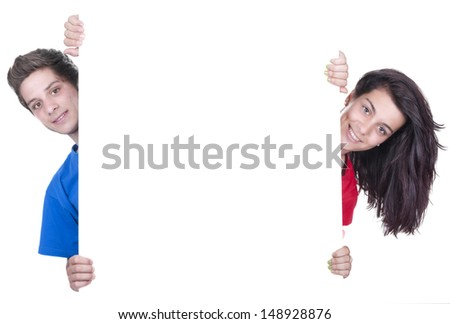 two smiling teenagers holding at a blank board  - stock photo