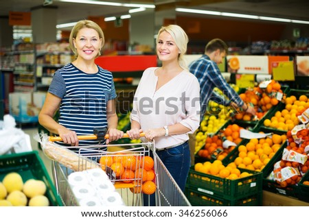Two smiling woman choosing seasonal fruits in grocery section of supermarket