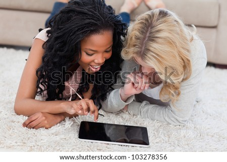 Two smiling women are lying on the floor are using a tablet