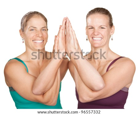 Two smiling women perform entwined namaskar over white background
