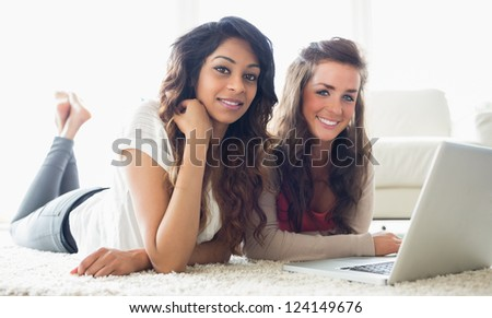 Two smiling women typing on a computer while lying on the floor in a living room - stock photo