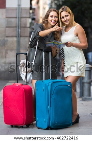 Two smiling women with baggage checking route outdoors - stock photo