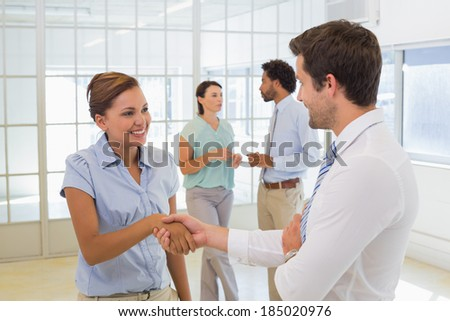 Two smiling young business people shaking hands with colleagues in background at the office - stock photo