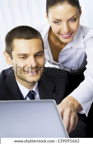 Two smiling young businesspeople working with laptop at office