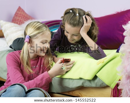 Two smiling young girls in bedroom looking at mobile phone - stock photo