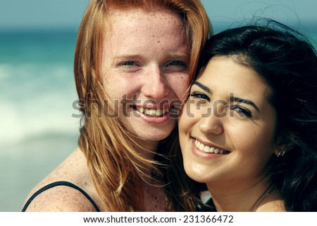 two smiling young teenage girlfriends on the beach - stock photo