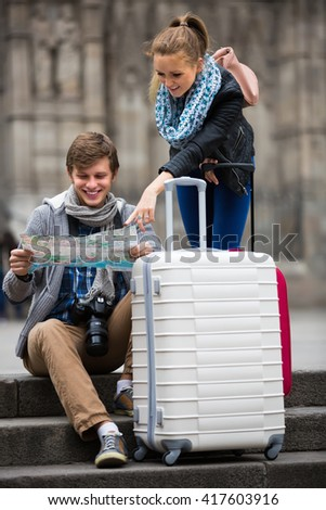 Two smiling young travelers with city map and baggage looking for hotel - stock photo