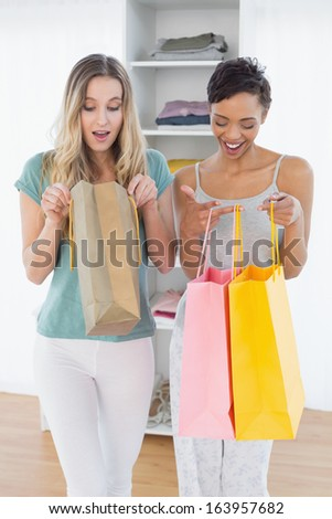 Two smiling young women looking into shopping bags at home