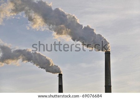 Two Smoke Stacks Polluting the Air Horizontal - stock photo