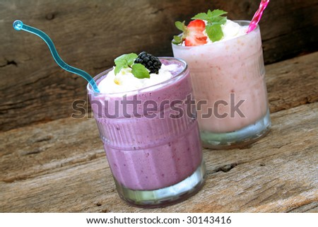 Two smoothies one blackberry and one strawberry. The main focus is on the blackberry smoothie. - stock photo