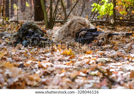 Two sniper in camouflage suits with rifles in hands hide in the woods/Team of snipers aiming at target in forest - stock photo