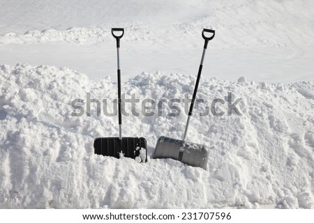 Two snow shovels for snow removal in deep fresh snow. - stock photo