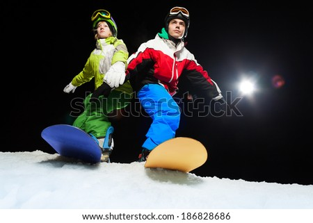 Two snowboarders ready to slide at night - stock photo