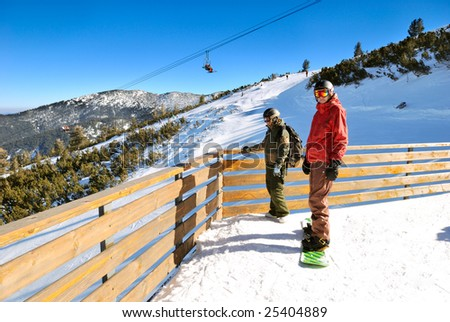 Two snowboarders - young man and woman - on the ski slope