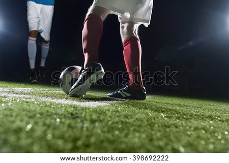 Two soccer players kicking a soccer ball - stock photo