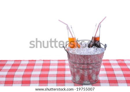 Two soda bottles in bucket of ice on checkered table cloth isolated on white - stock photo