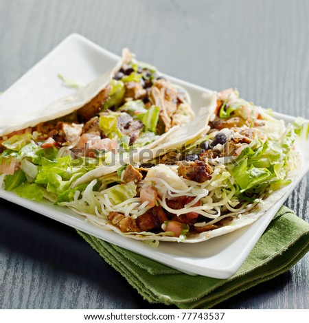 two soft shell chicken tacos plated with a napkin. Selective focus on front taco - stock photo