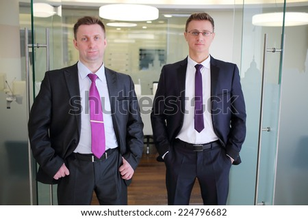Two solid businessmen in suit standing at entrance to conference hall - stock photo