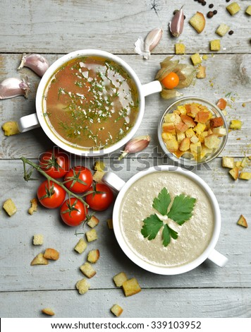 Two soup bowls composition vegetarian mushroom and fish cream soup in bowl with garlic parsley dill and croutons on rustic wood background - stock photo