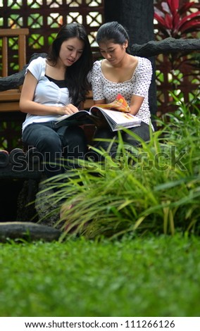 Two southeast asian girls having fun reading and sharing information they found on a book/ magazine.