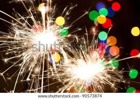 Two sparklers and background with colorful bokeh - stock photo