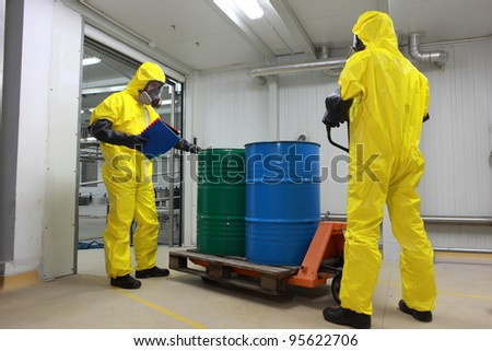 Two specialists in protective uniforms,masks,gloves and boots  transport barrels of chemicals on forklift in factory - stock photo
